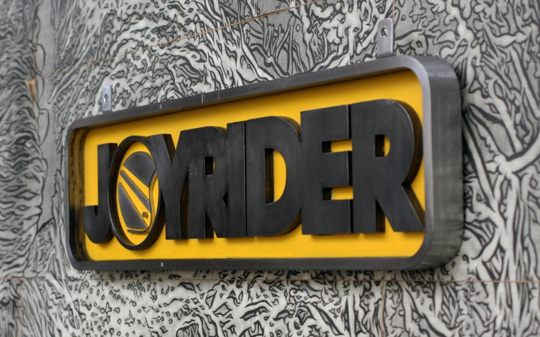 Finished Joyrider sign by Type Design, hung on a wall