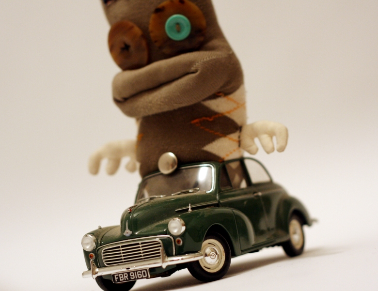'I' character from Mocorico children's book series, a sock puppet riding in a toy car
