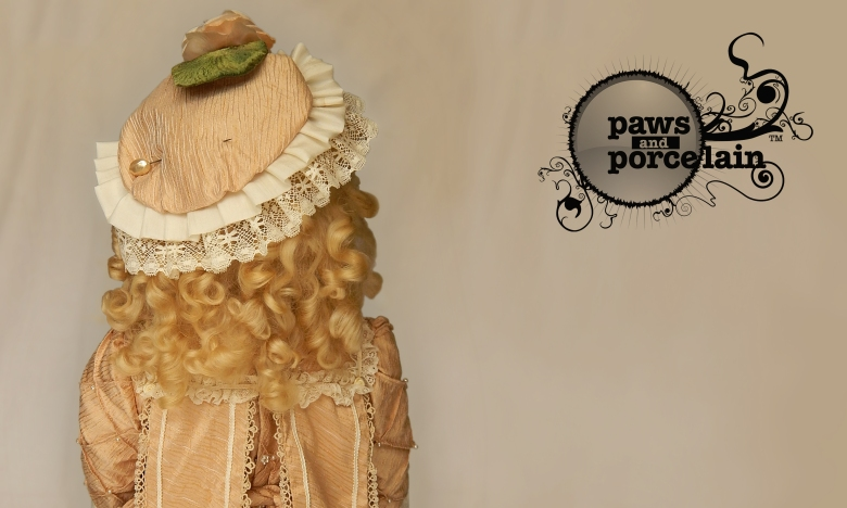 Paws and Porcelain branding with photograph of porcelain doll wearing pinned hat